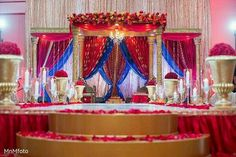 Love this grand stage design | Red and blue drapery amongst the gold pillars and stage decorations | Red orange and yellow floral decorations | gold and crystal chandelier | Stage Décor Ideas | Indian Wedding Ideas | Credits: MmMfoto | Every Indian bride's Fav. Wedding E-magazine to read. Here for any marriage advice you need |www.wittyvows.comshares things no one tells brides, covers real weddings, ideas, inspirations, design trends and the right vendors, candid photographers etc.