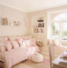 Dormitorio infantil en tonos pastel rosa claro con muchos cojines sobre la cama y paredes con papel pintado_00160571