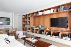 A wall-spanning bookshelf made of Freijo, a strong hardwood found in the lower Amazon, brings warmth into the living area while providing an organizing structure for Hess's personal momentos.  built in cabinetry storage wood floating shelving and media tv console