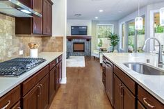 This sleek contemporary kitchen opens to a great room and outdoor space. New homes in the Peacock Meadows community built by RM Homes. Gig Harbor, WA.