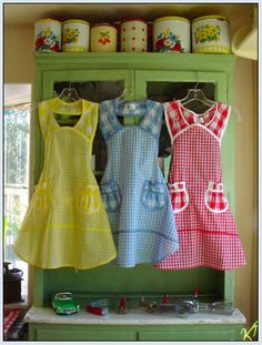 Oh, I love these gingham aprons. Particularly the red. I'd have to do chicken scratch embroidery on the pockets and hem though!