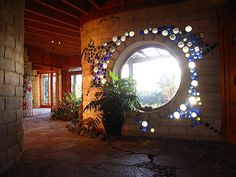 Beautiful glass bottle detail around the window. Perfect for brightening hallways of an earthship!