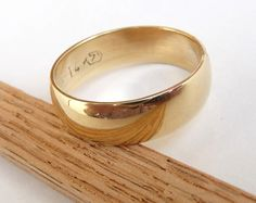 Men gold wedding band polished shiny domed 14k yellow gold wedding ring for woman and man. $590.00, via Etsy.
