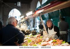 VENICE, ITALY - APRIL 1, 2014: An unidentified merchant sells fish at the fish market to unidentified customers, on April 1, 2014 in Venice,...