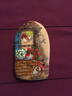 Painted rock with little cottage window and garden with a cut little bicycle.
