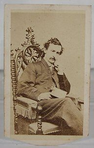 1860's CDV of John Wilkes Booth, Assassin of President Abraham Lincoln. Booth captured here seated in a fancy, Gothic style chair, holds a book while presenting a studious and thoughtful appearance. Little did his many theatre fans know of his soon to be revealed dark side.