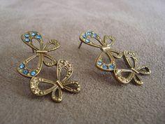 Brinco em metal ouro velho, no formato de borboletas, com aplicação de strass Swarovski azul e dourado. R$28,00
