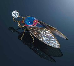 Multi-gem brooch, by Wallace Chan designed as a cicada holding a cushion-shaped diamond, the head and body set with black opal and lapis lazuli with carved amethysts atop, to the cabochon ruby eyes and pink sapphire detail, extending to the white to grey crystal and mother-of-pearl wings with titanium veins, mounted in titanium and 18k gold, signed Wallace Chan. Image Christies