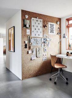 Home Office con un gran muro de corcho para pinchar fotos, ideas, adornos, etc. La silla de escritorio combina perfecto con el color del corcho y el marco de madera de la ventana.