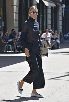 Accessories are all aces: Olivia matched her white bow-topped loafers with a cream and black bag