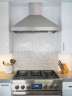 Geometric cooktop backsplash tiles in gray and white bring attention in a subtle, stylish and appealing way between stainless steel appliances.