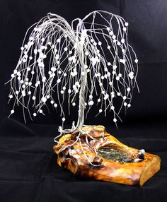 The tree in the photo is not the one being sold, these trees are made to order. This is a hand wrapped Weeping Willow wire tree, using Stainless Steel Wire. Set upon a piece of driftwood from the coastal areas of British Columbia. A water like feature with rocks and a small