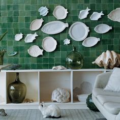 A set of fish plates is mounted against an oceanic backdrop of cool-colored tiles. They are grouped by color and streamlined into a cascading flow -- just like a school of fish swimming in unison underwater.