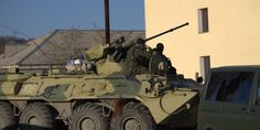 BELBEK AIRBASE, Crimea, March 22 (Reuters) - Russian troops forced their way into a Ukrainian airbase in Crimea with armoured vehicles, automatic fire and stun grenades on Saturday, injuring a Ukrainian serviceman and detaining the base's commander f...