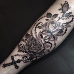 """Tatuajes de rosarios Descubre las mejores fotos de tatuajes de rosarios La palabra rosario se deriva del nombre latino """"rosarium"""", que significa """"corona de rosas"""". El rosario se encuentra en casi todo tipo de religiones como la cristiana, la judía, el islamismo o el hinduismo, aunque de forma tradicional representa la fe"""