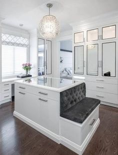 Luxurious walk-in closet boasts an ornate chandelier hung over a mirror top white center island finished with satin nickel pulls and a built-in bench topped with a gray velvet tufted cushion.