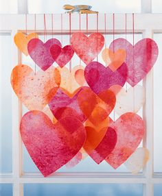 Cute v-day back drop idea. Hanging crayon hearts DIY from  Martha Stewart.  trap medium amount of crayon shavings between large sheet of wax paper folded over.  Use similar colors or make a rainbow!  then iron between craft paper (to protect iron and surface) until shavings are melted, let cool, and cut out desired shapes.  hang with silk ribbon.
