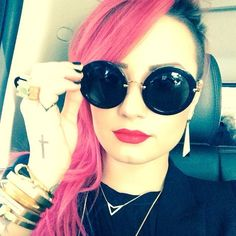 Demi Lovato looks amazing with pink hair and round shaped sunglasses.