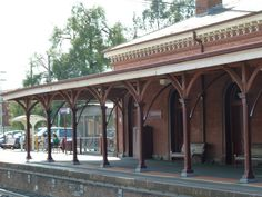 Castlemaine Railway Station - Victoria Australia. Platform 1 and main station building seen from Platform 2. Located in the centre of the state, Castlemaine is a sophisticated town in a stately 19th century setting with grand buildings and stately gardens that reflect the opulence and architecture of the boom time during the gold rush of the 1800s. The region also has a strong reputation in the arts with musicians, instrument makers, craftspeople and artists who have helped shape the area