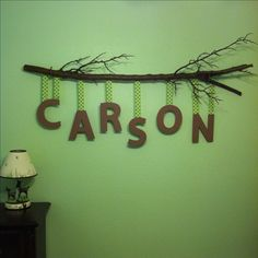 I made this for my baby boy's room using a branch from my husband's parents' property (sprayed with lacquer), ribbon, hot glue and painted the $1.99 letters from Hobby Lobby, the brown paint my dad had used to paint trees on his other wall :) Hung with bike hooks (also painted brown) and the whole thing cost about $19 :)