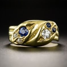 Although sparkling with 100 year old diamonds, the hallmarks indicate that this Victorian style classic from Great Britain was produced during the latter-twentieth century (although we would never know otherwise). One serpent is diamond crowned with sapphire eyes, the other vice-versa. Crafted in rich, buttery 18K yellow gold. Currently ring size 6 1/2.