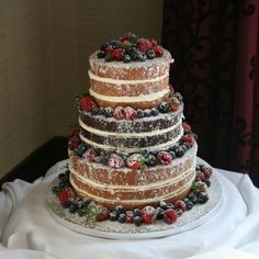 Three tier 'naked' wedding cake in chocolate & vanilla sponges decorated with a sprinkling of icing sugar & fresh berries.