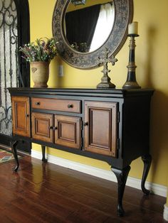 Nice wood buffet in a sleek black distressed finish. Four raised panel cabinets and 1 drawer are a nice glazed wood with a pretty wood inlay pattern. Stands on elegant legs. Could also work as an entry table, hall table or console, hang a plasma above.