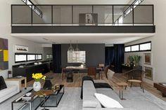 Le designer et architecte brésilien Diego Revollo a conçu l'aménagement et la décoration des pièces de cet appartement à São Paulo. L'habitation, de style loft, dispose désormais d'un charme sophistiqué avec un mélange d'éléments modernes et industriels.  Des couleurs neutres comme du gris, du noir et du bleu marine sont couplées avec de l'acier et du bois afin de proposer un jeu de textures intéressant. La cuisine, élégante et minimale en noir mat est située sous la mezzanine...