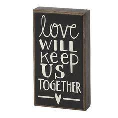 """Charming box sign is a celebration of the love you two share. Made of solid wood with distressed paint and text stating """"Love Will Keep Us Together"""" with a heart at the bottom. Measures 6. 1/2. in x 3"""