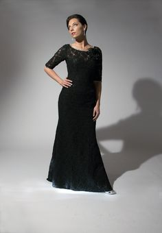 Long Sleeve Special Occasion Gown  Eugenia style 193. Sleek black lace with sheer lace sleeves and lace flower broach. Crystal beaded trim around neckline and sleeves.