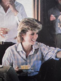 Diana while on an official tour; handing out birthday cake to a staff member on board their Royal flight.