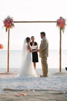 Colorful Isla Mujeres Destination Beach Wedding. The ceremony on the beach had flower vases marking the aisles and a bamboo ceremony structure with gorgeous, lush flower arrangements on each corner of peonies, ranunculus, roses ,tulips in vibrant pinks, corals, peach and yellow.  Jessica Arden Photography http://www.confettidaydreams.com/colorful-isla-mujeres-destination-wedding/