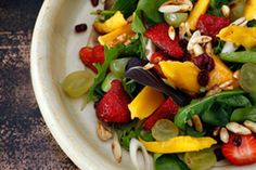 This summer salad is made extra colourful with the addition of strawberries and mango. You could also add some avocado slices. It's colourful and festive looking, a great salad to make on a large platter and serve with cold meats or simple grills.
