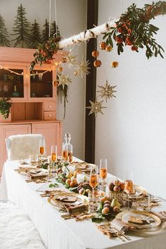 It's coming to that time of year! A boho-ho holiday party with hanging decorations and orange themed table settings.
