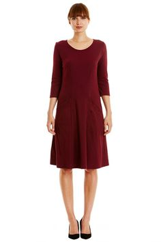 Burgundy flared dress in 100% organic certified cotton. Below knee length with front pockets and long sleeves. Also available in dark green. Length 103cm.