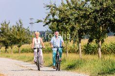 Senior Frau und Mann auf Fahrrad Tour an einem Feld im Sommer