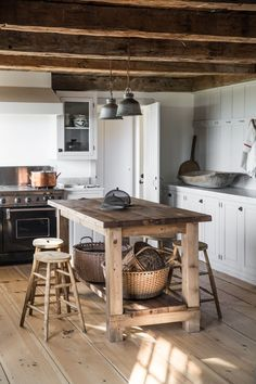 One side of the kitchen is lined with peg rails. The round baskets beneath the island store clean dish towels. The wooden stools are vintage finds and the wire baskets were sourced from Trillium Soaps in Rockland, Maine. Rustic Country Kitchens, Farmhouse Kitchen Island, Modern Farmhouse Kitchens, Home Kitchens, Kitchen Islands, Small Kitchens, Rustic Cottage, Kitchen Rustic, Rustic Farmhouse