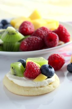 Mini Sugar Cookie Fruit Pizzas start with a soft sugar cookie topped with a cheesecake layer and are finished with some fresh fruit.