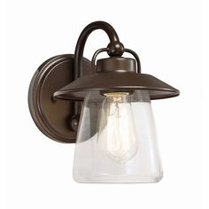 This transitional 1-light wall sconce features a mission bronze finish that will complement many decors throughout your home. The clear glass shade enhances the light and completes the look of this versatile piece.