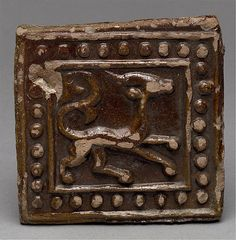 "Afganistan C12th C13th Square Tile Met Museum -A  series found in Ghazni, the capital of the Ghaznavid dynasty (977–1186), in a house destroyed during the Mongol invasion of 1221. Most of the tiles in the series are square, some are polygonal, and are molded in relief with animals, plants, or occasionally inscriptions. Their decoration shows affinities with classical pre-Islamic motifs from Iran, such as the ""pearl"" borders and the animals in profile within a frame."