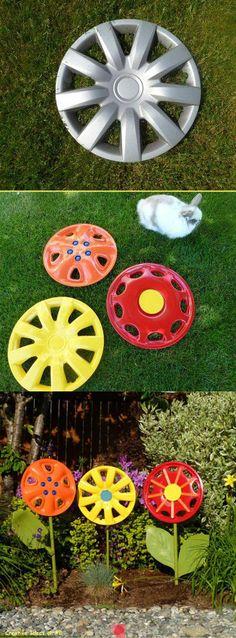Repurpose hubcaps into yard art! Metal structural garden flowers <3