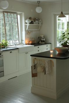dark counter, white cabinets, painted floor and open shelves