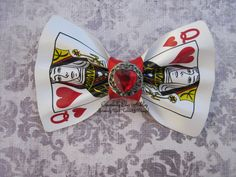 Premade and ready to ship.  3.5 wide and 2.25 long    Super cute and unique hair clip. This is perfect for Alice in Wonderland fans or attending an Alice in Wonderland theme party.    This is a real poker playing card that has been carefully folded to give a nice smooth bow appearance. Satin like red ribbon center with an red heart gem embellishment. . All of this is attached to a ribbon lined double prong alligator clip.          Dont see what you are looking for? Message me, we do custom…