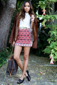 Brown leather jacket, red skirt, handbag, blask shoes. Summer fashion. Street clothing