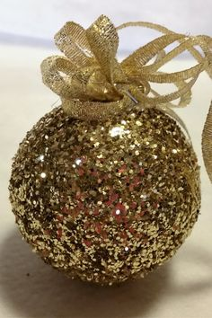 Gold glittered round ornament with gold bow