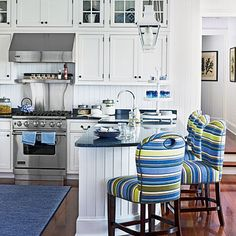 A sea-inspired color scheme sets the stage for a few decorative nods to maritime life in this Jersey Shore kitchen, where a pair of lanterns hangs above a rounded, hull-like breakfast bar. Barstools upholstered in a crisp blue-and-acid green stripe add a jolt of color.