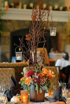 Arrangement of roses celosia cymbidium and vanda orchids lotus pods eucalyptus and Manzanita branches / http://www.deerpearlflowers.com/50-vibrant-and-fun-fall-wedding-centerpieces/