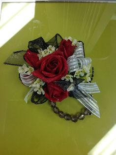 Red roses in a wrist corsage with wax flower and white ribbon accents. Placed on a Fitz design  black bracelet .