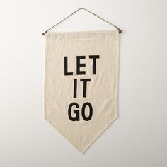 LET IT GO Wall Banner _ Artist Ashley Brown Durand crafted this Schoolhouse Electric exclusive from repurposed, soft cotton flour sacks. She carefully hand cuts each letter from 100% wool and hand stitches them using cotton thread.