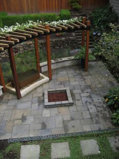Detail of area without furniture. Back yard space for entertaining includes a gas fire-pit, infinity-edge water fountain, and curving steel and cedar pergola. Floor is paved with Cut Bluestone and features a soft green divider. Rain garden helps collect and divert water around the patio and down the slope.